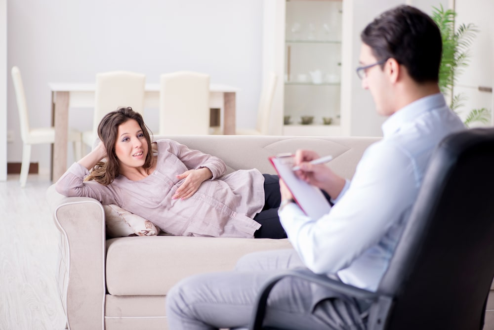 Pregnant woman lying across couch with one hand on her belly speaking with a therapist who is taking notes.