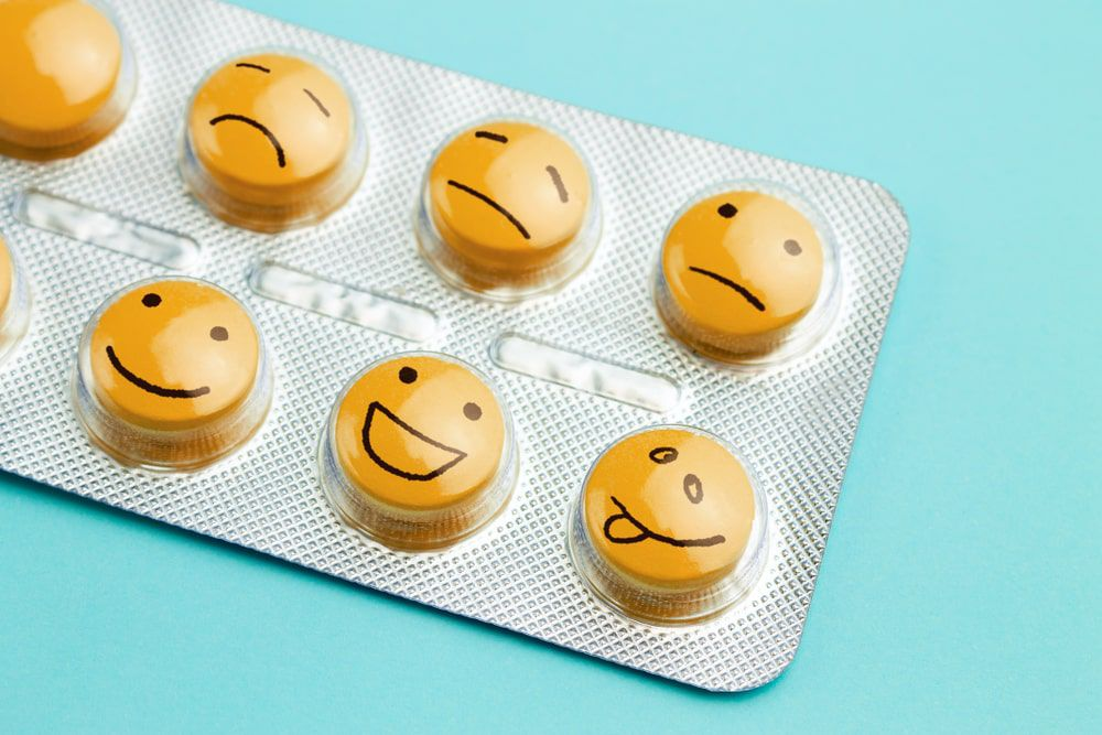 yellow antidepressant pills with emoticon faces in a foil pack against a sky blue background