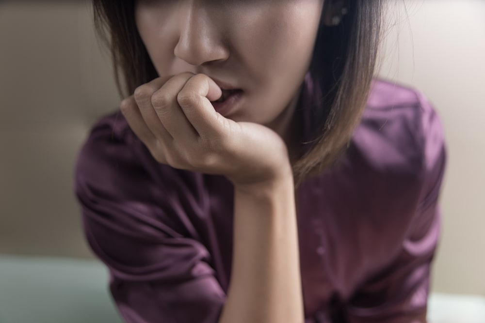 Closeup of a woman biting her nails with an anxious expression looking off into the distance