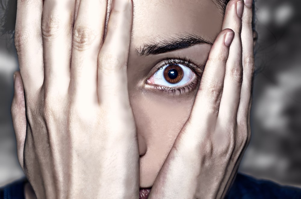 Woman holding both hands over her face, only peeking out with one terrified-looking eye
