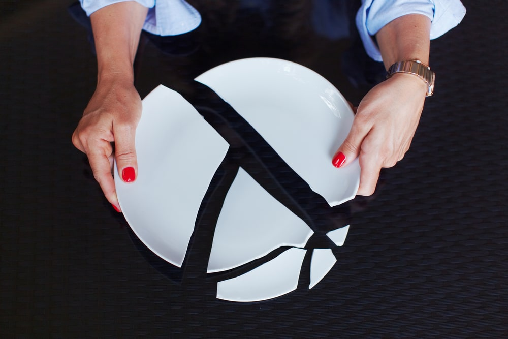 Woman holding pieces of a white broken plate against a black background
