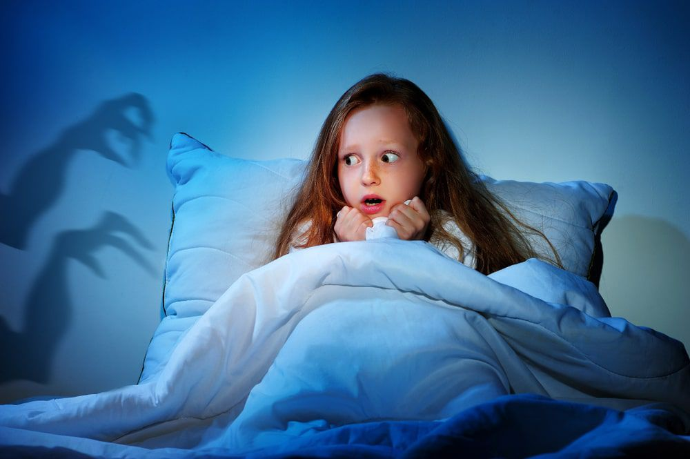 Little girl sitting in bed holding the covers to her face and looking scared with shadows on the wall next to her
