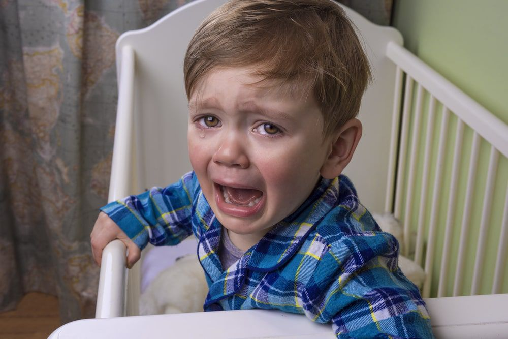 Distressed toddler screaming and crying while standing inside his crib