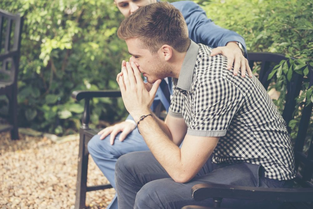 Two guys sitting on a bench with one providing emotional support to the other