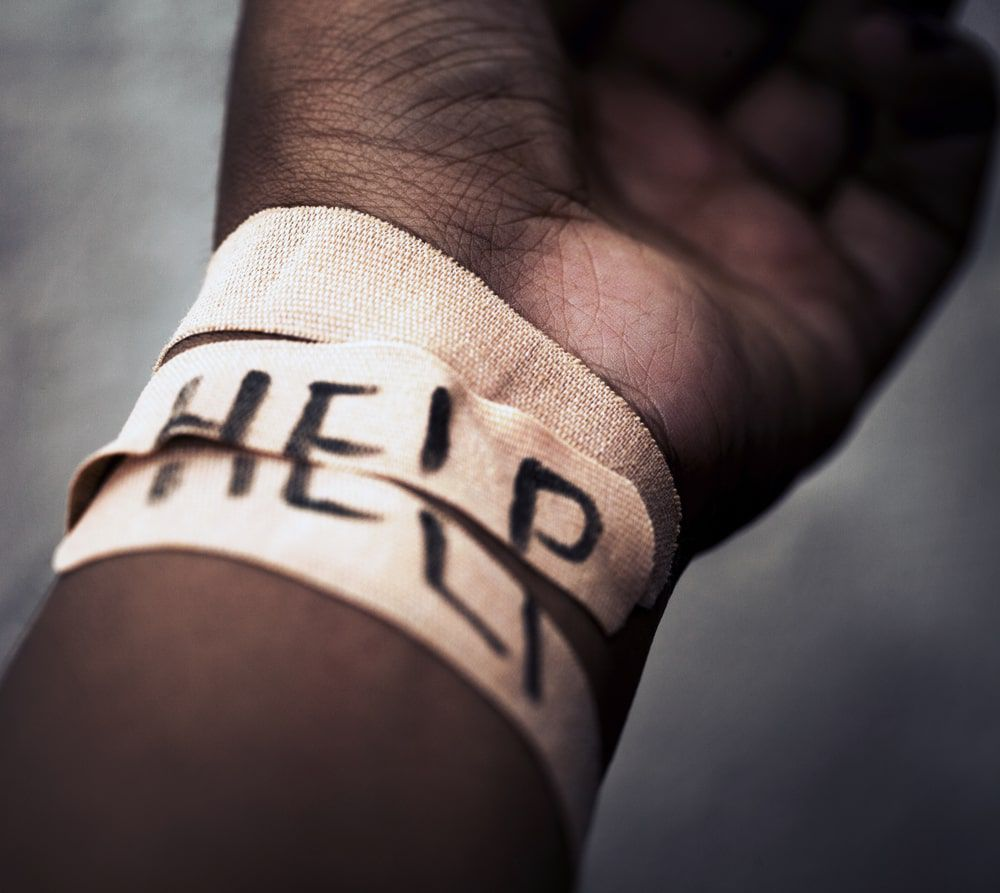"Arm facing upwards with wrist bandaged and the word ""help"" scribbled across the bandages"