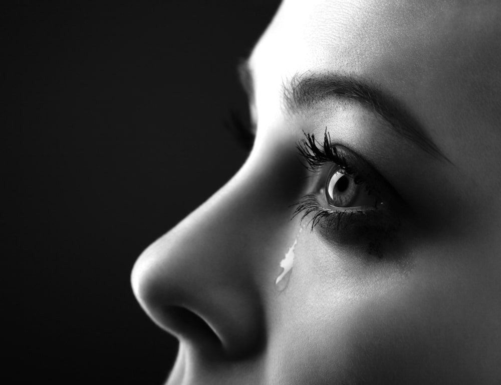 Black and white sideways closeup of a woman's eye and tear falling down her cheek