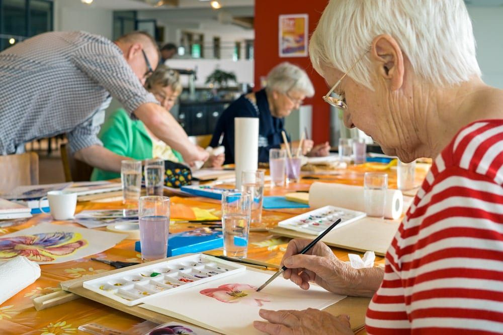 Senior citizens performing art therapy through painting