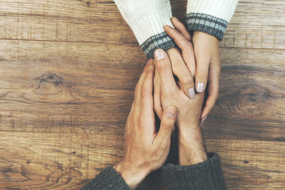 Couple holding hands across a wood tabletop
