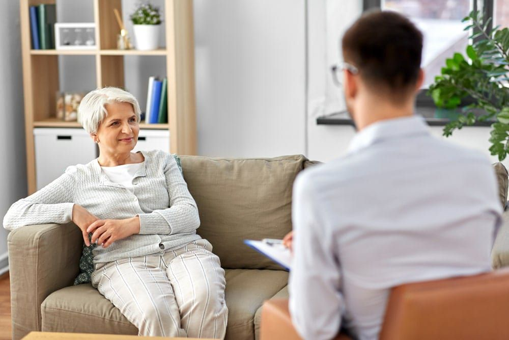 Geriatric psychiatrist talking with a female patient