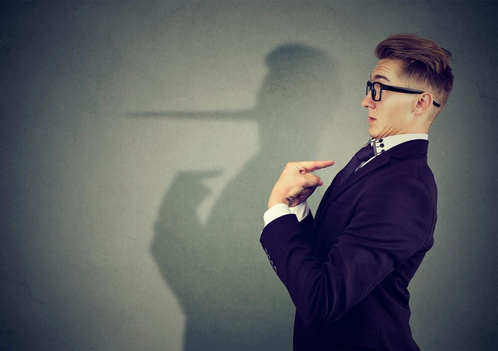 Man pointing at himself innocently as his shadow shows his nose growing to indicate a lie