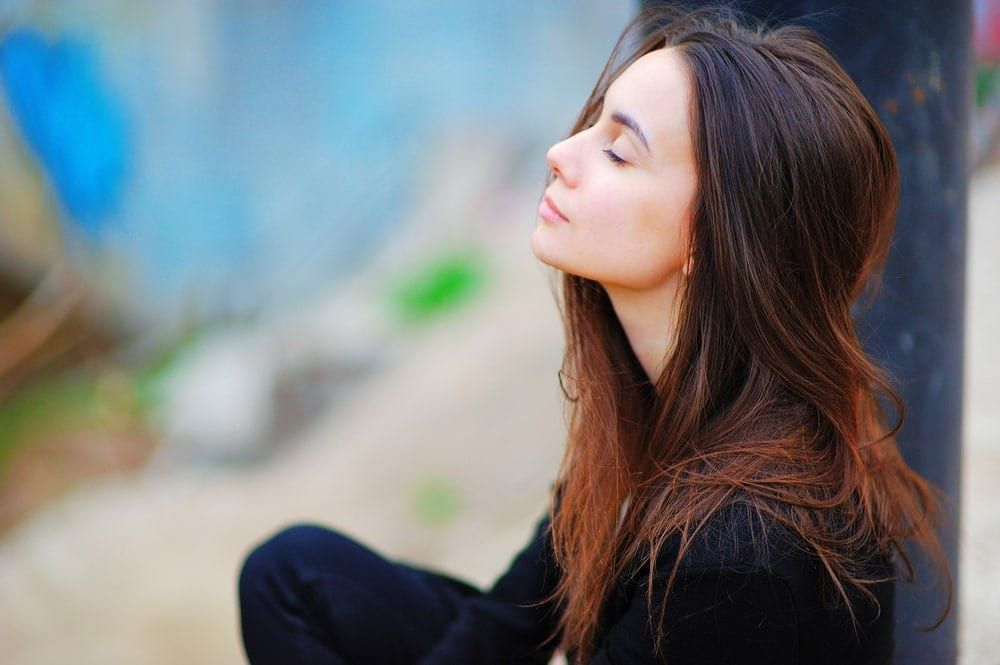 Mindful woman sitting with her eyes closed and head tilted upward