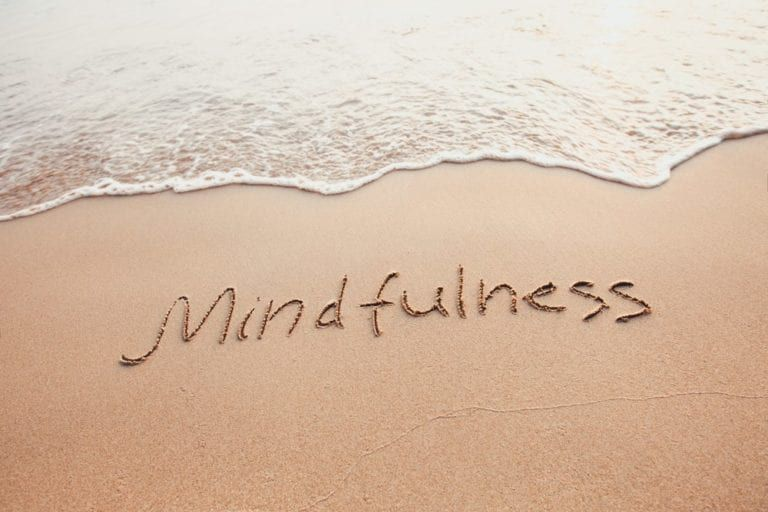 """The word """"mindfulness"""" written in the sand at the beach"""