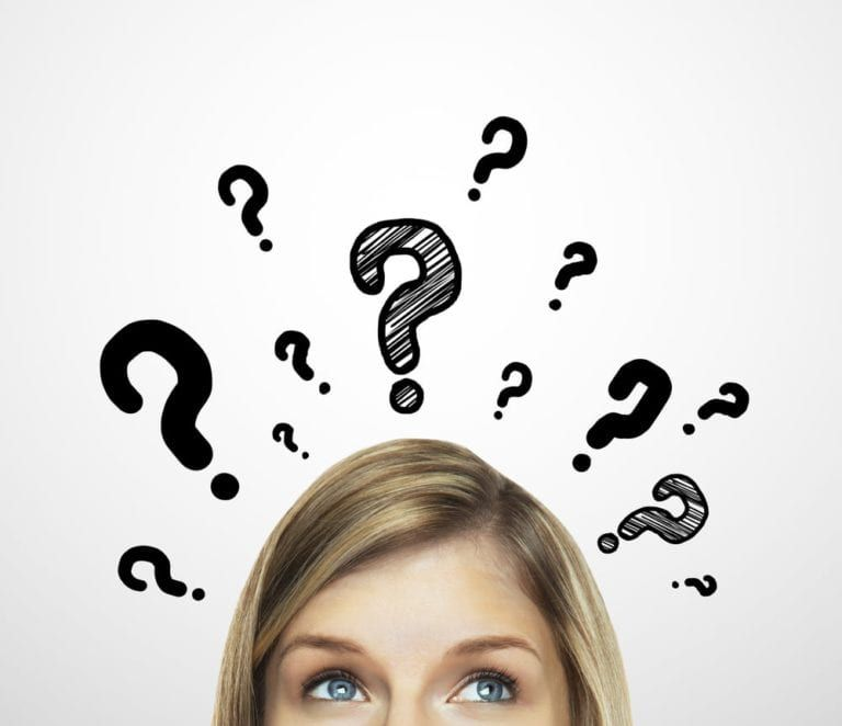 Upper half of woman's face surrounded by question marks