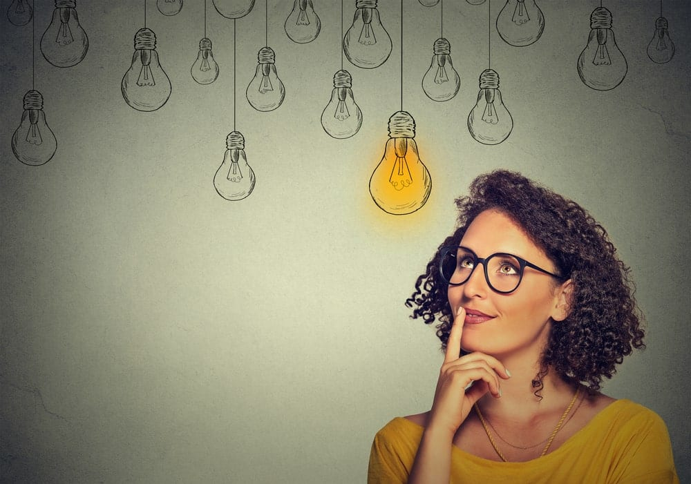 Woman thinking and looking up towards a lightbulb