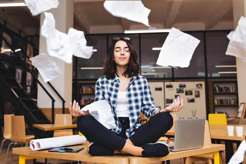 Woman meditating on her desk surrounded by work stress