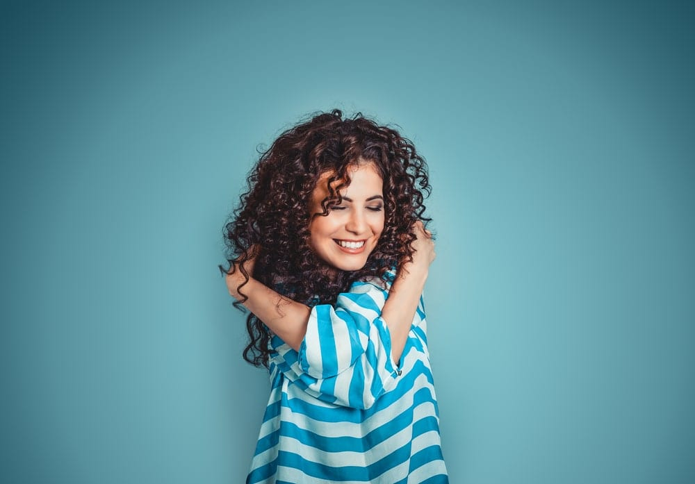 Woman hugging herself and smiling