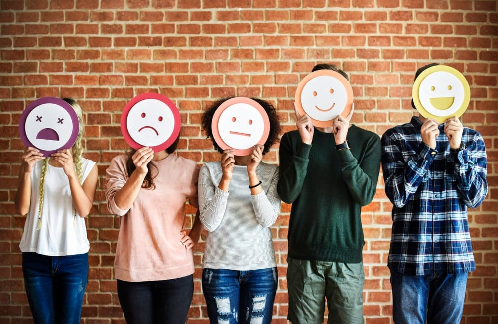 five people standing beside each other wearing masks of different emotions