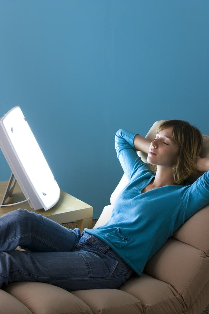 Woman relaxing in a chair next to her therapy light box
