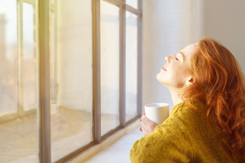 Woman basking in the sunlight through her window