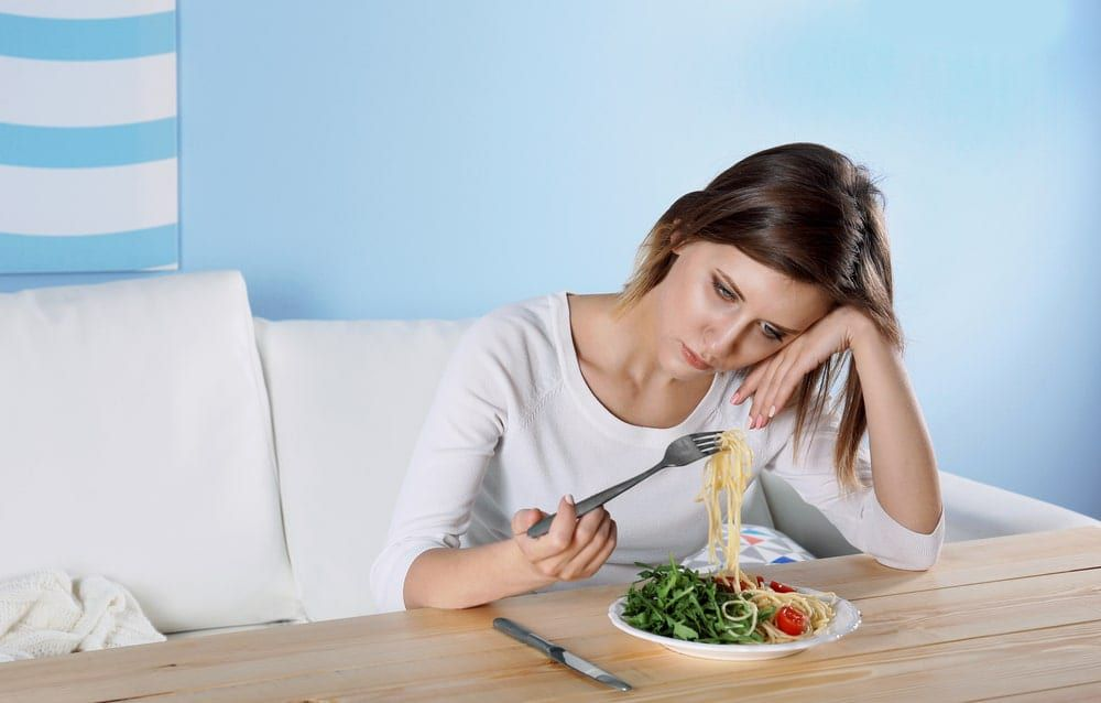 Girl struggling to eat a plate of food in front of her