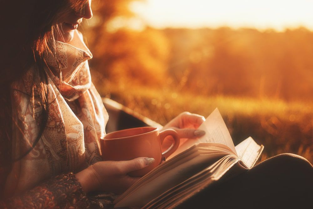 Woman relaxing with a book and a hot drink