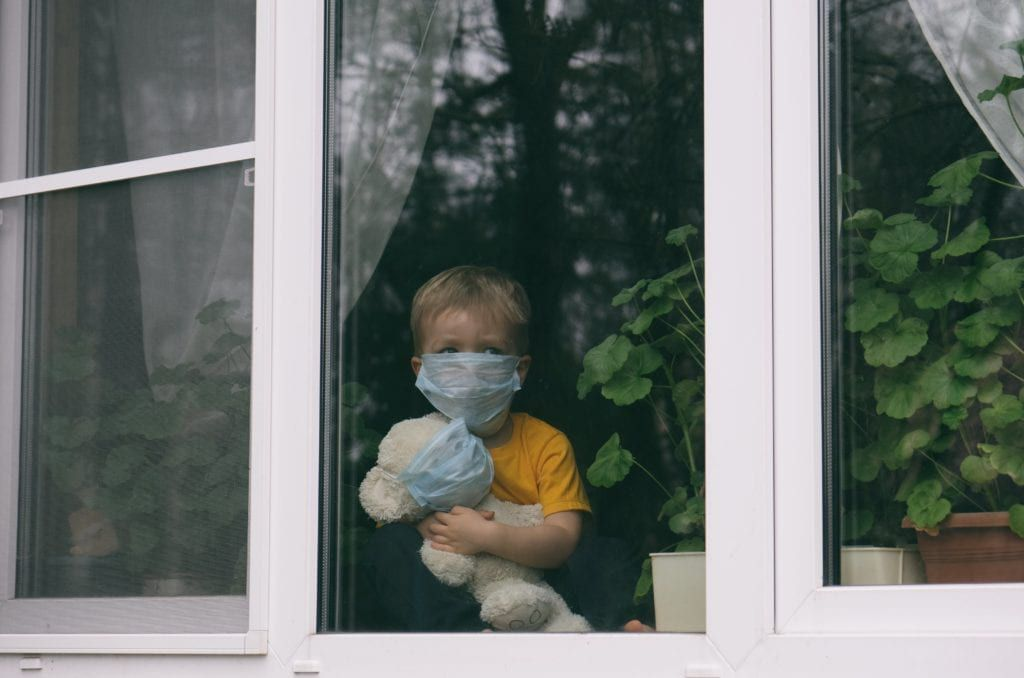 young boy sitting inside looking out the window with a mask on himself and his teddy bear