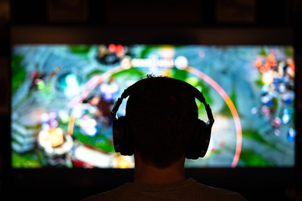 silhouette of a male head with headphones looking at a video game screen