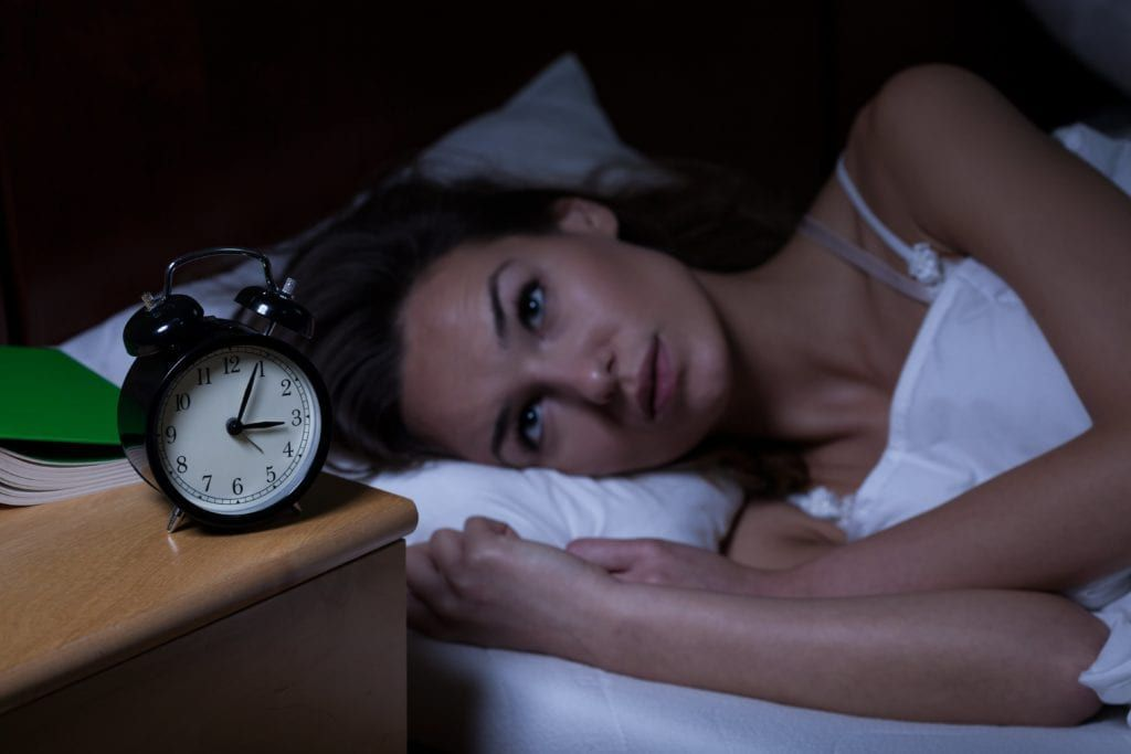 woman who can't sleep and is staring at the clock