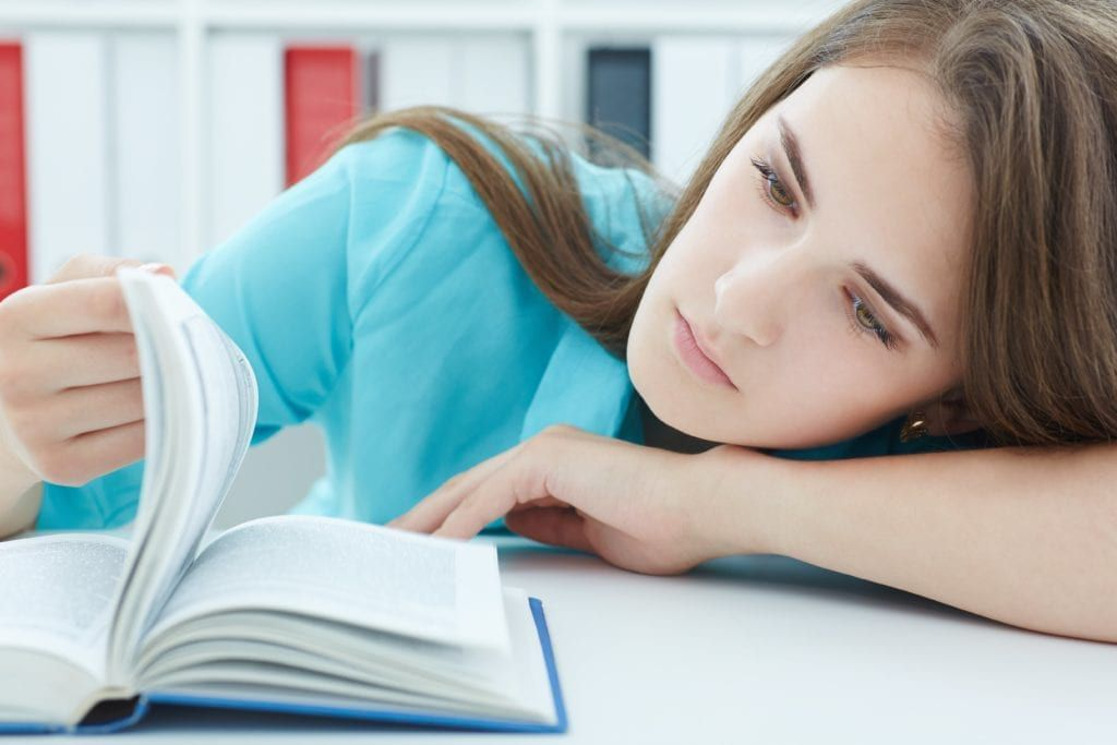 Woman looking apathetic while trying to read a book