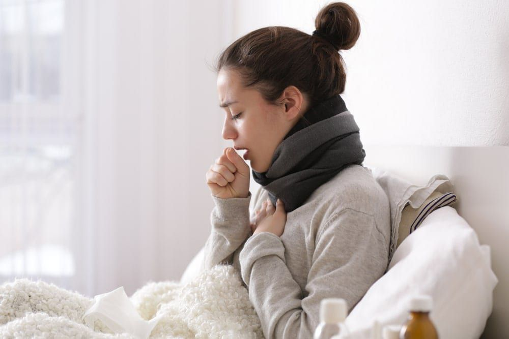 young woman sick in bed holding her chest and coughing