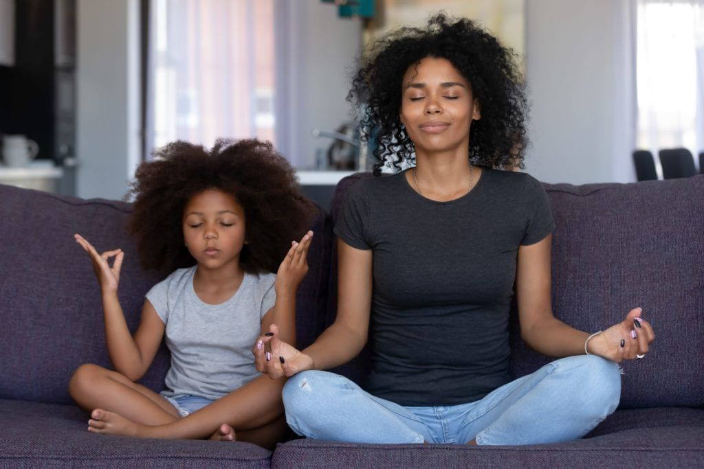 mother and daughter meditating on the couch