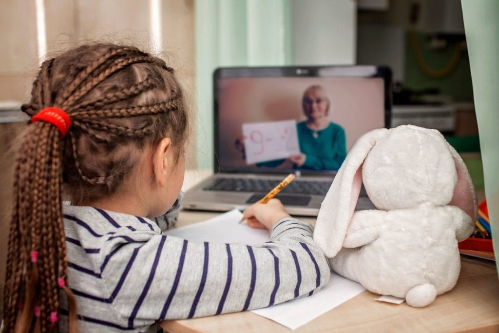 young girl doing distance learning with her stuffed bunny