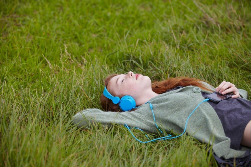 girl laying alone in the grass listening to music