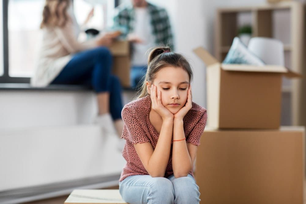 young girl looking sad sitting next to moving boxes with her parents in the background