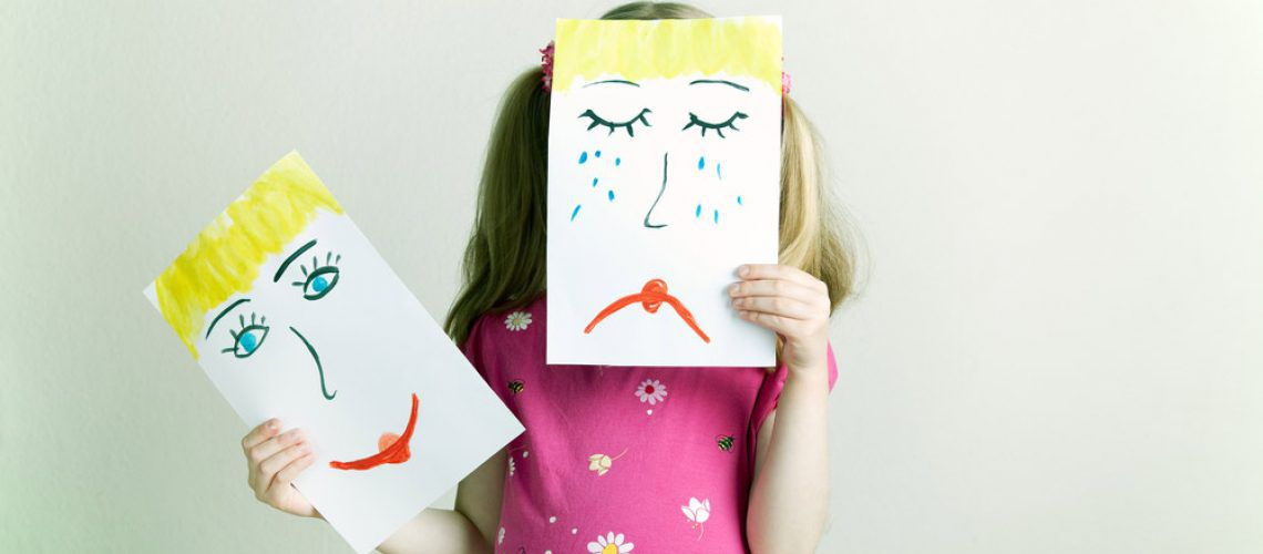 little girl holding up drawing of sad and happy faces