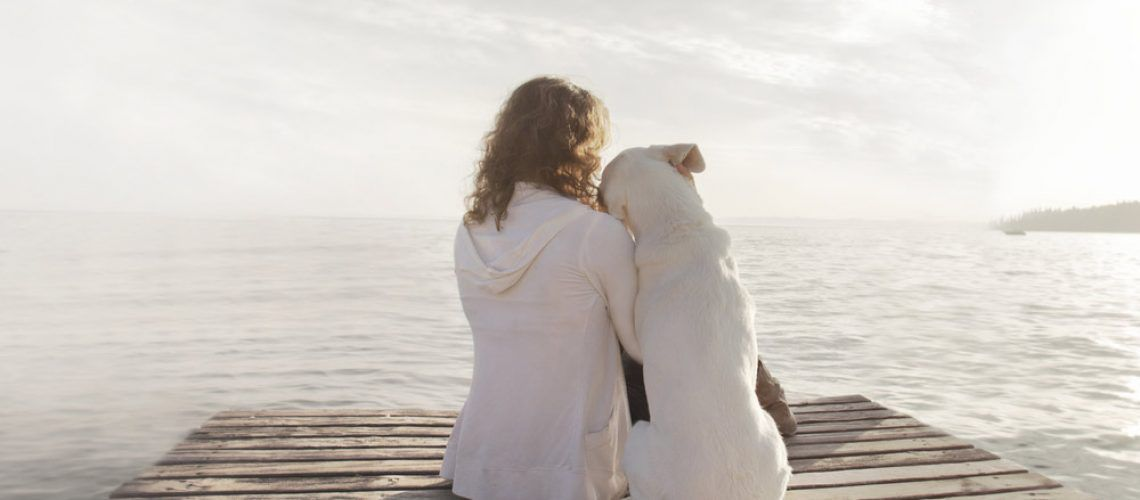 dog and woman sitting on dock