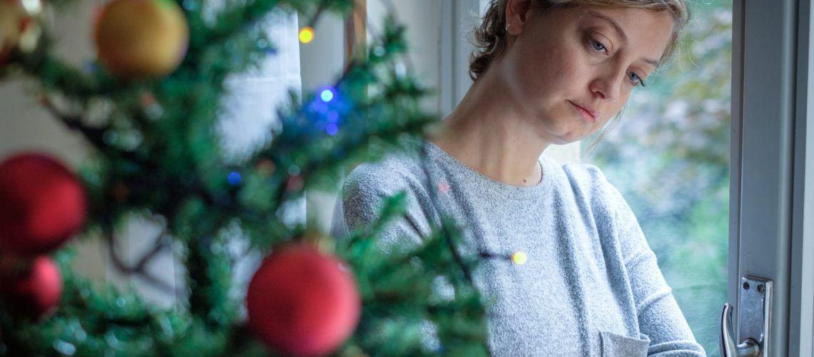Woman looking down near Christmas Tree