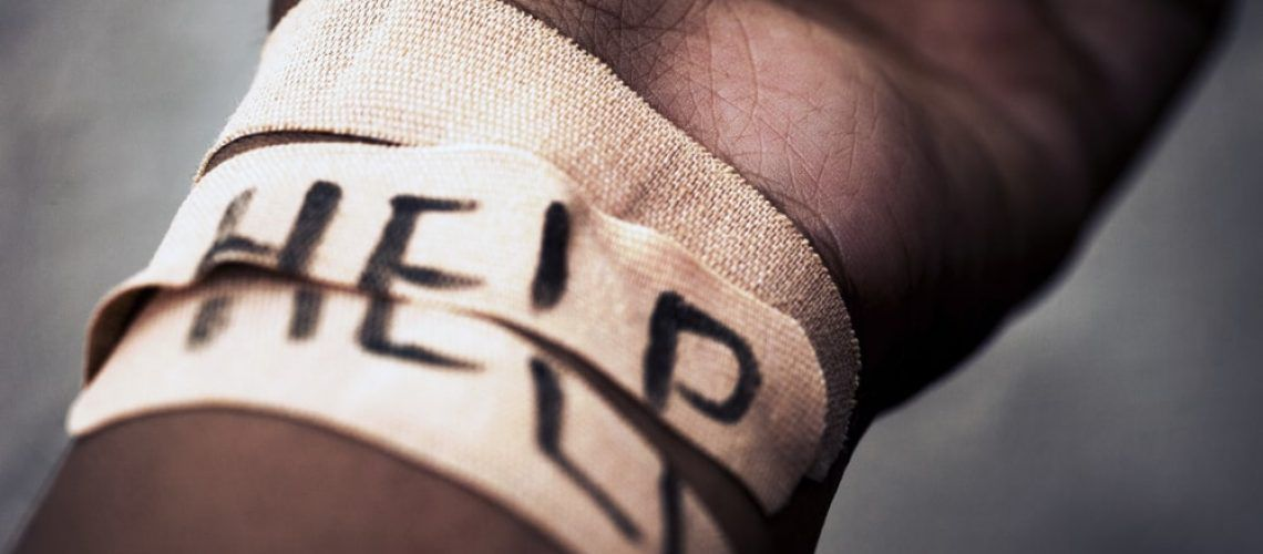 Arm facing upwards with wrist bandaged and the word