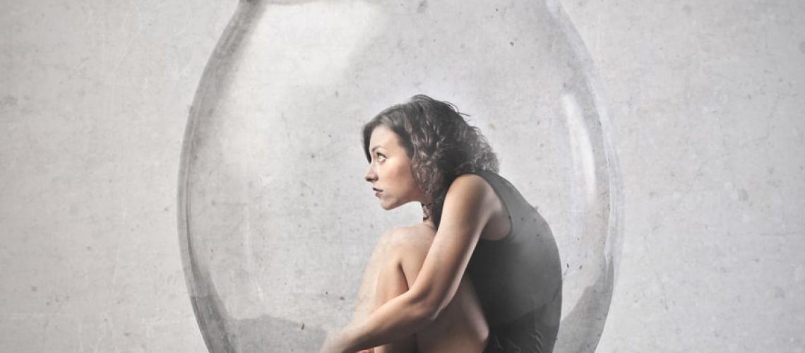 Woman sitting in the fetal position inside a giant glass jar